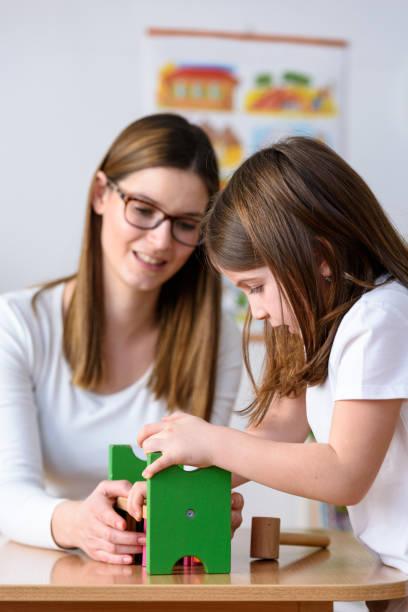 frau kind spielt mit didaktischen bunten spielzeug drinnen - vorschule betrachten - erzieherin stock-fotos und bilder