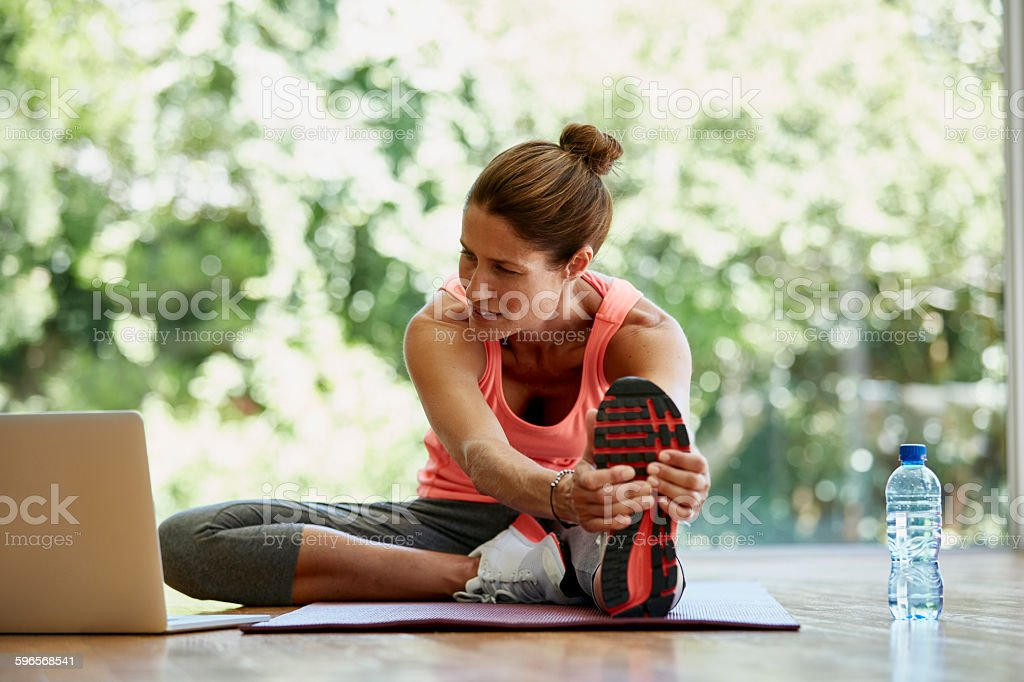 Woman looking at laptop while exercising at gym stock photo