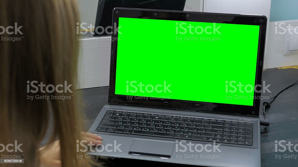 Woman looking at laptop with green screen stock photo