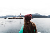 Woman looking at lighthouse from the ship at the Beagle Channel