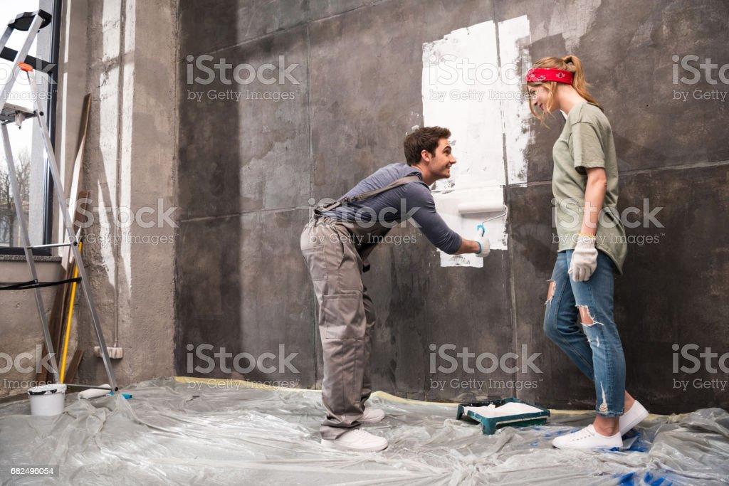 woman looking at man painting wall, renovation home concept foto de stock libre de derechos