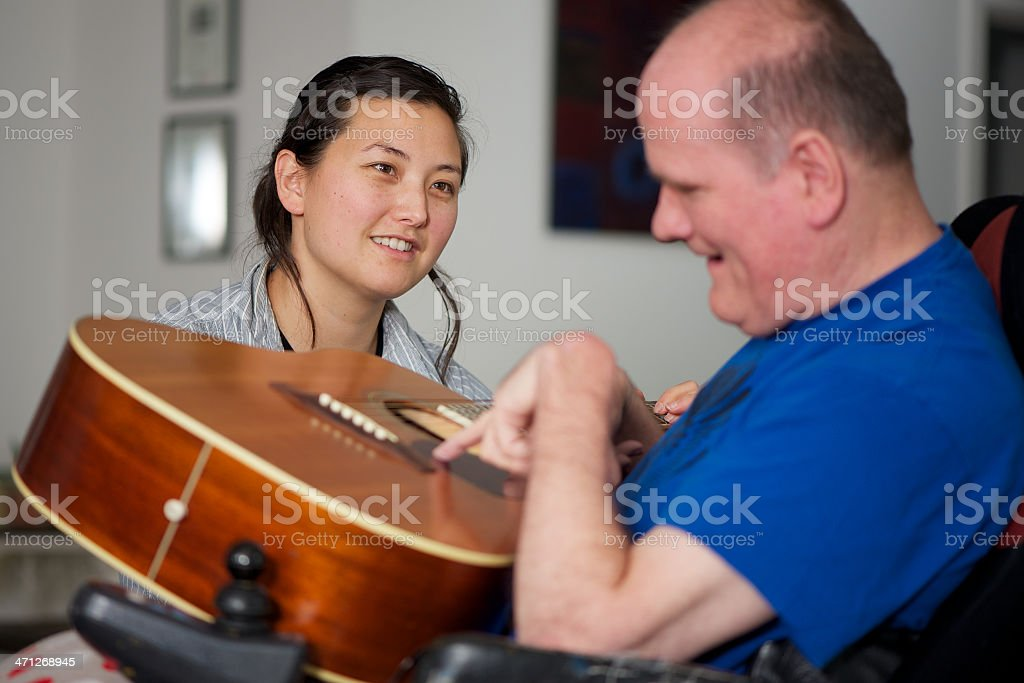 Woman looking at Man with a Disability Play Guitar stock photo