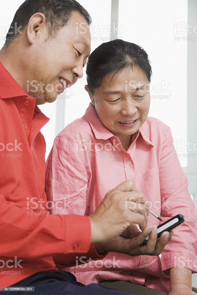 Woman looking at man's palmtop royalty free stockfoto