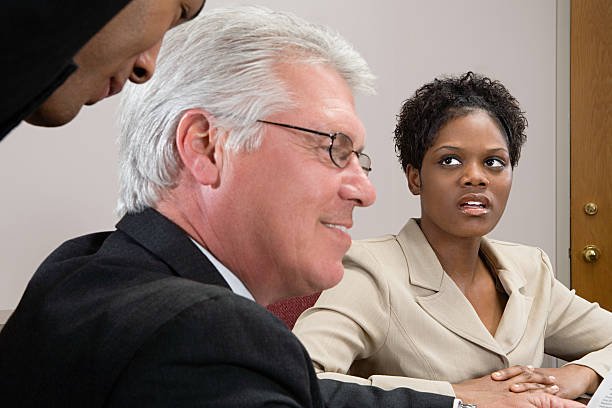 Woman looking at men whispering Woman looking at men whispering sex discrimination stock pictures, royalty-free photos & images
