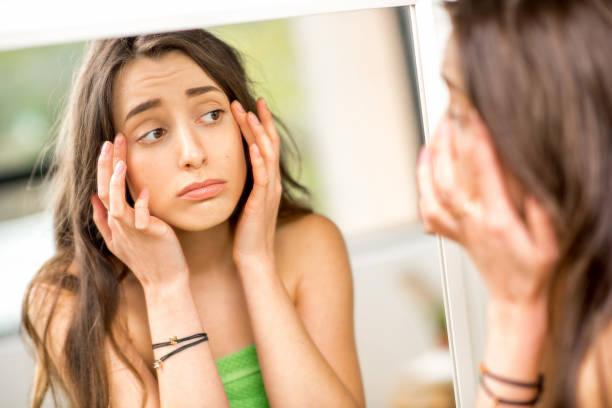 浴室の鏡を見ている女性 ストックフォト