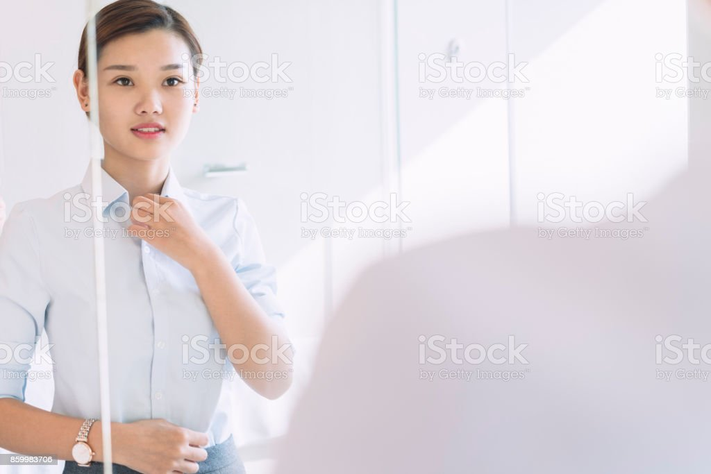 woman looking at mirror in the bathroom stock photo