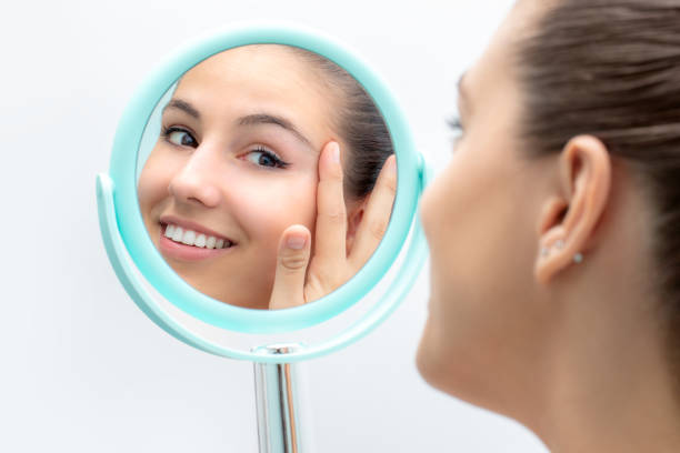 Woman looking at mirror touching skin. stock photo