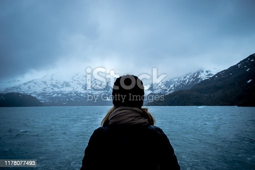 Woman doing a cruise and looking at the Portage glacier in Alaska with snowcapped mountains in background.