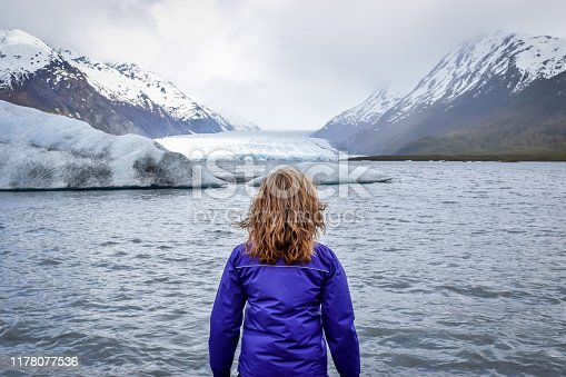 Woman looking at snowcapped mountains by the Spencer glacier in Alaska.