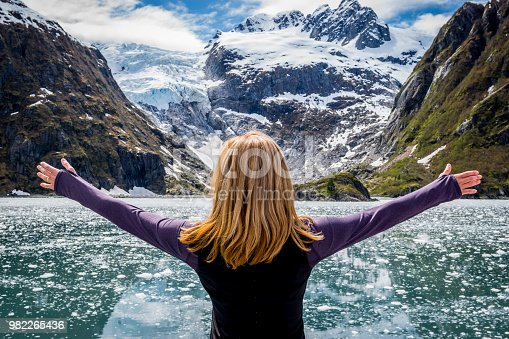 istock Woman looking at mountain range and glacier 982265436
