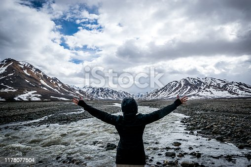 Woman with arms outstretched looking at Toklat River and snowcapped mountains of the Denali National Park and Preserve in Alaska.