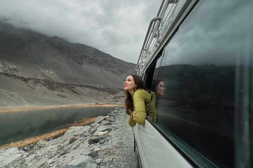 Young Caucasian woman looking at mountains of Northern Pakistan from window in the van