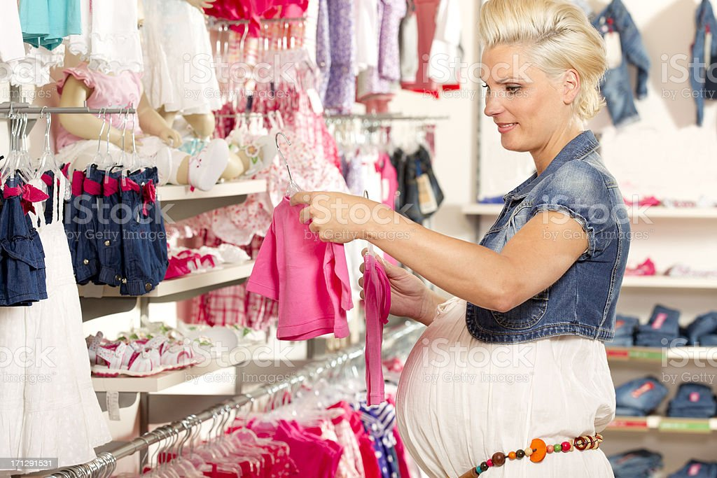 Woman looking at new baby clothing stock photo
