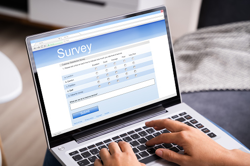 Woman Looking At Online Survey Laptop Computer At Home