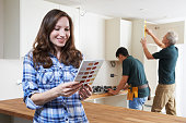 istock Woman Looking At Paint Chart In New Kitchen 505625280
