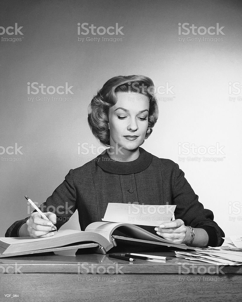 Woman looking at paper, holding pencil royalty-free stock photo