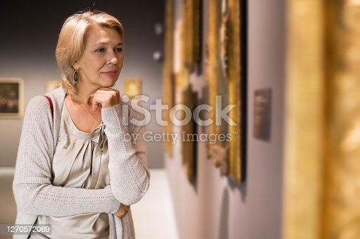 Portrait of mature woman near picture collection in the museum