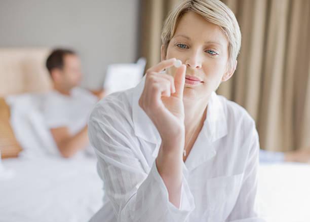 Woman looking at pill stock photo