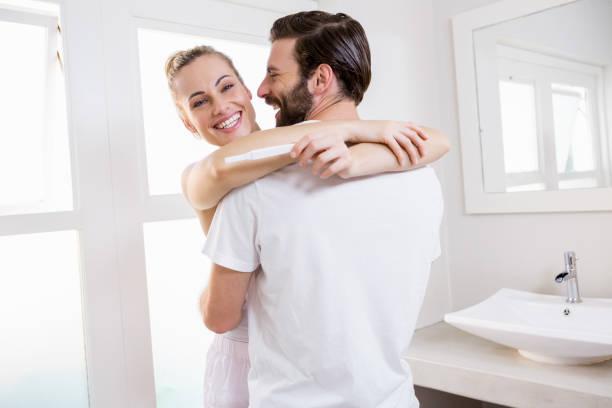 mulher olhando para o teste de gravidez enquanto abraçando um homem - happy test results - fotografias e filmes do acervo