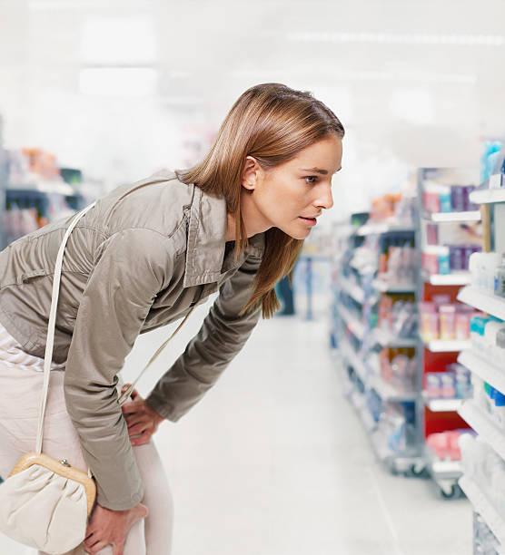 frau blickt auf produkte in einer apotheke - drogerie stock-fotos und bilder