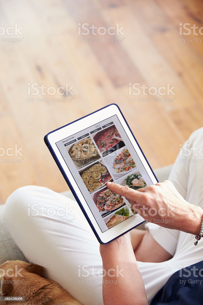 Woman Looking At Recipe App On Digital Tablet stock photo