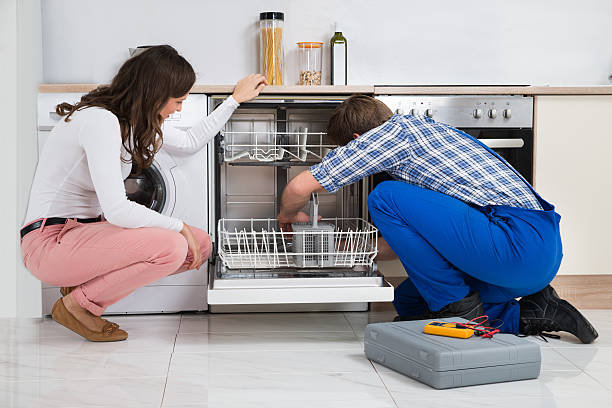 woman looking at repairman repairing dishwasher - gender stereotypes stock pictures, royalty-free photos & images