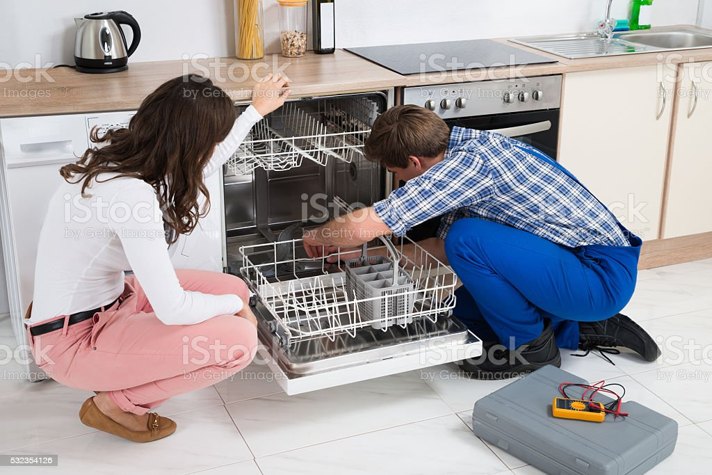 Woman Looking At Repairman Repairing Dishwasher stock photo