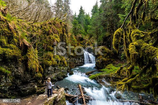 istock Woman looking at rocky waterfall 999127242