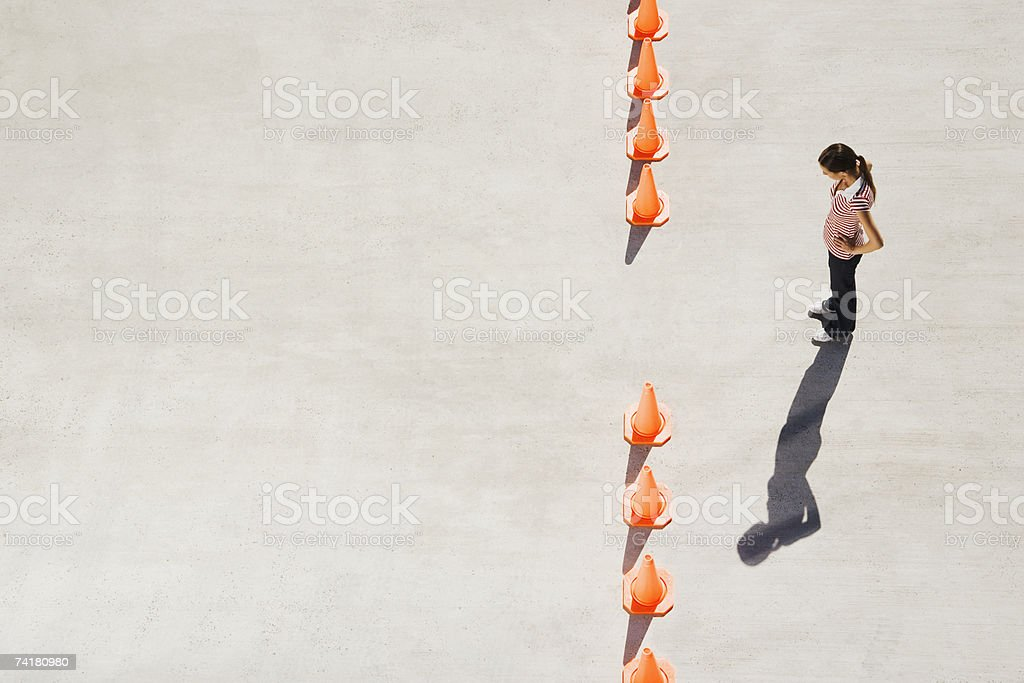 Woman looking at row of traffic cones with gap royalty-free stock photo