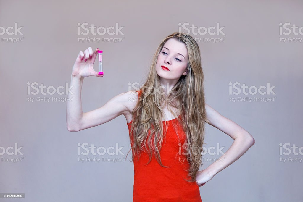 Woman Looking At Sand Watch in Her Hand stock photo
