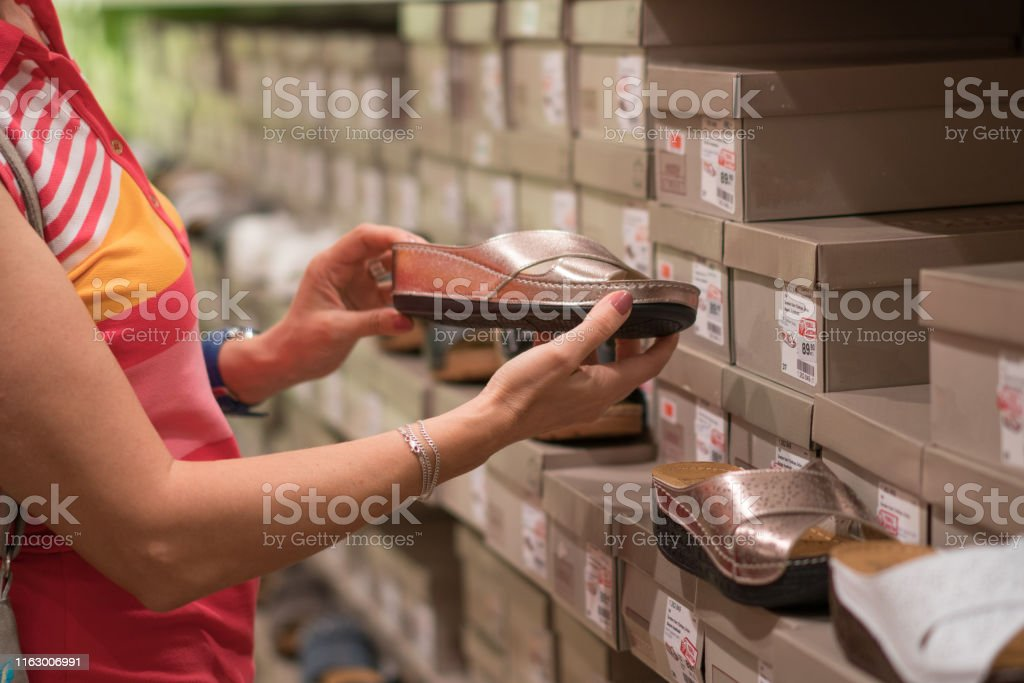Woman looking at sandal in Shoe Store, close up