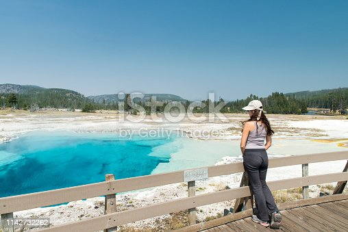 Woman looking at Sapphire Pool  hot spring in Yellowstone National Park