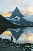 Young Caucasian woman looking at scenic view of lake near Matterhorn mountain in Switzerland