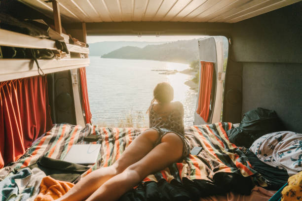 Woman looking at scenic  view of Lake of Sainte-Croix from campervan Young Caucasian woman looking at scenic  view of Lake of Sainte-Croix from campervan rv interior stock pictures, royalty-free photos & images