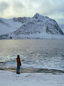 Woman looking at  seaside in winter on Lofoten island