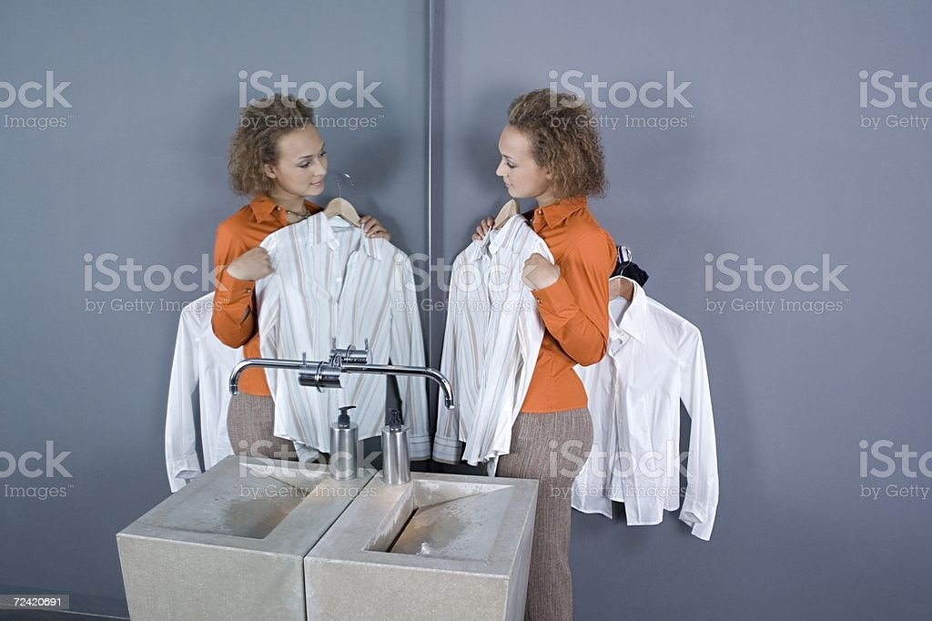 Woman looking at shirts in restroom mirror royalty-free stock photo