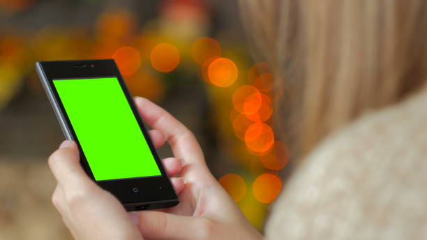woman looking at smartphone with green screen - green screen background stock photos and pictures