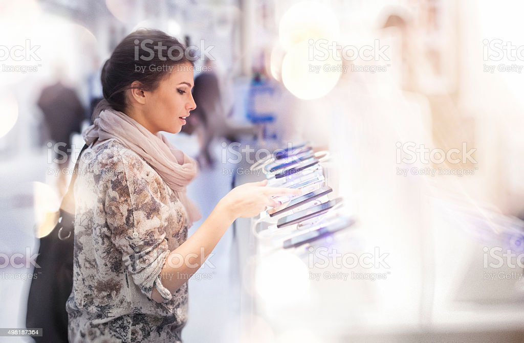 Woman looking at smartphones in store! stock photo