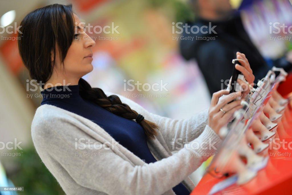 Frau auf der Suche auf smartphones im store! – Foto