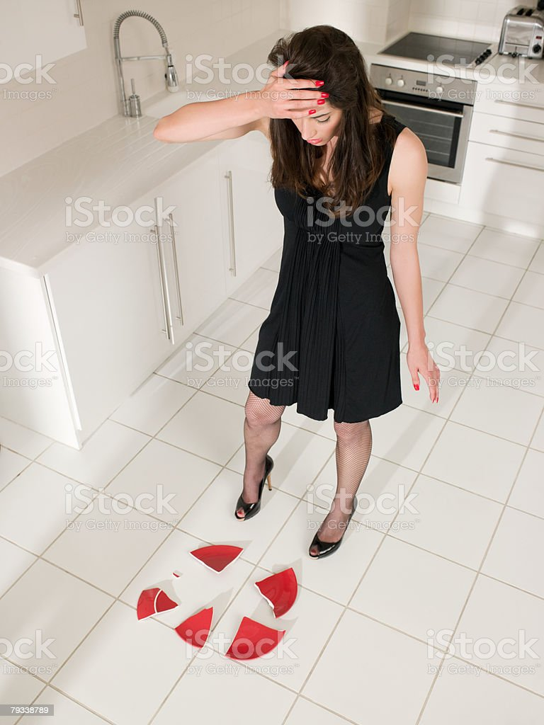 Woman looking at smashed plate on floor royalty-free 스톡 사진