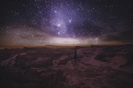 Woman looking at star sky at canyon in Atacama Desert