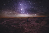 Woman enjoying stargazing under the night sky with million of stars and Milky Way at beautiful canyon on Atacama Desert in Chile