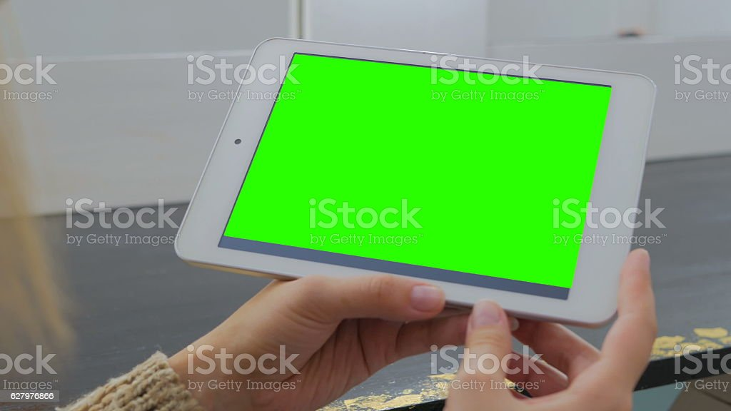 Woman looking at tablet computer with green screen stock photo
