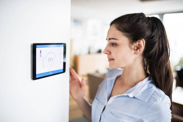 A woman looking at tablet with smart home screen. A woman looking at tablet with smart home control system. smart thermostat stock pictures, royalty-free photos & images