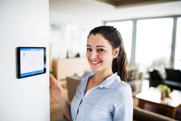 eine frau, die tablette mit smart home-bildschirm betrachten. - tablet mit displayinhalt stock-fotos und bilder