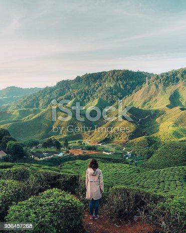 Young Caucasian woman enjoying scenic view of  tea plantations