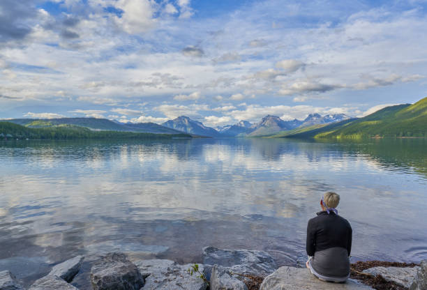 Woman Looking at the Beautiful Natural Scenery of Glacier National Park's Lake McDonald Area During the Summer in Montana, USA. stock photo
