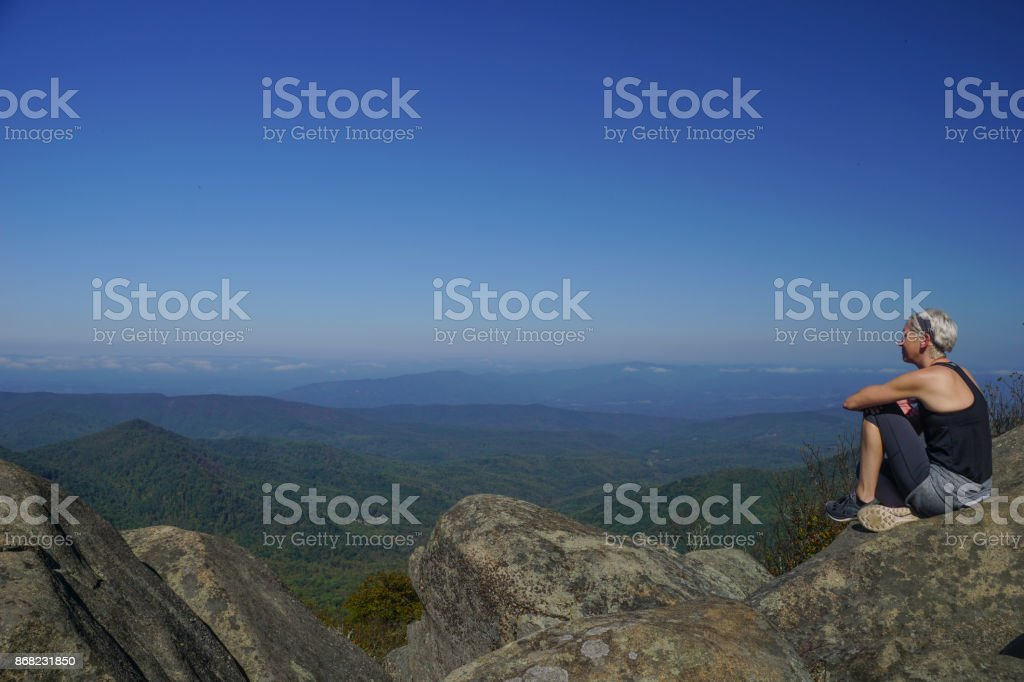 A woman sits on top of a peak looking at the beautiful natural...