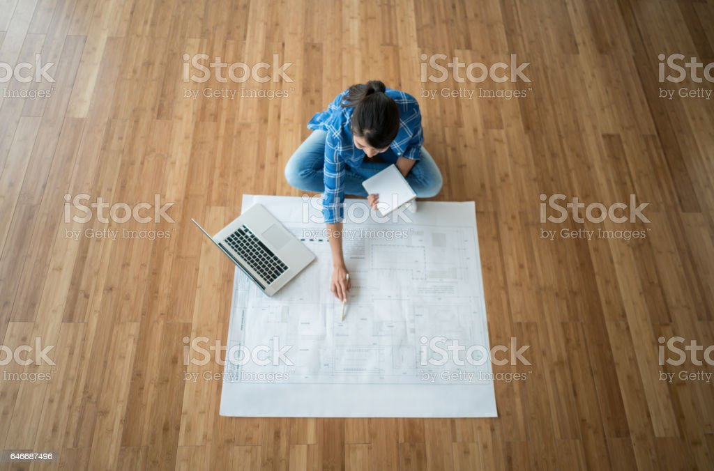 Woman looking at the blueprints of her new house stock photo