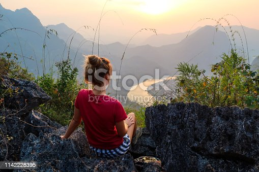 Woman looking at the charming view from hill, Nong Khiaw, Laos